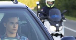 Jeune homme en voiture suivi de la police
